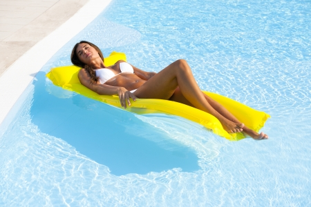 sunbathing: Beautiful woman relaxing and floating on pool, high angle view Stock Photo