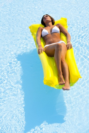 sunbathe: Beautiful woman relaxing and floating on pool, high angle view Stock Photo