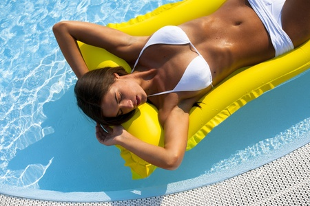 Beautiful woman relaxing and floating on pool, high angle view Standard-Bild