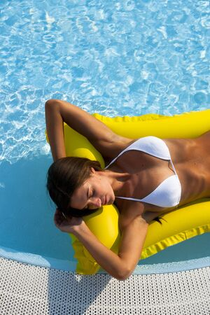 Beautiful woman relaxing and floating on pool, high angle view Stock Photo - 13245438