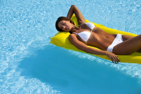matress: Beautiful woman relaxing and floating on pool, high angle view Stock Photo
