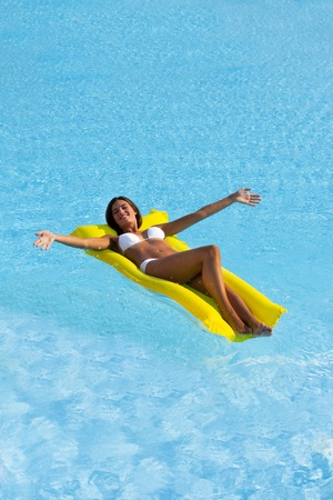 Happy Beautiful woman relaxing and floating on pool, high angle view photo