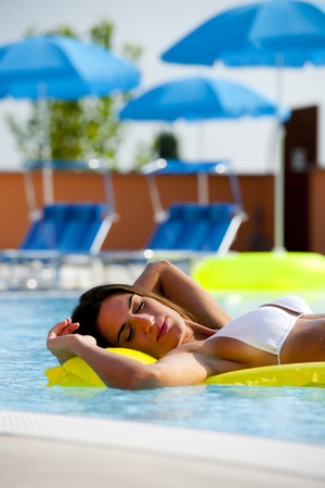 Beautiful woman relaxing and floating on pool, her eyes closed photo