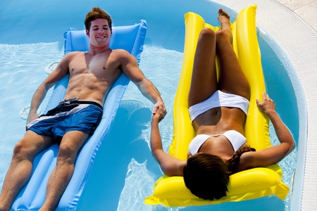Young couple enjoying floating on pool photo