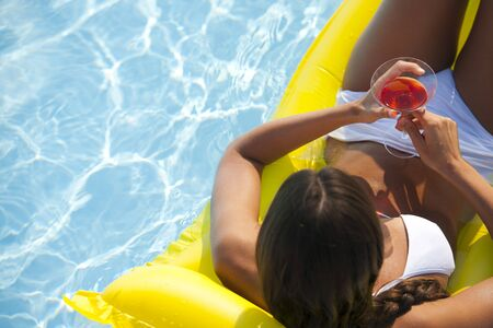 matress: Young woman relaxing on pool with drink