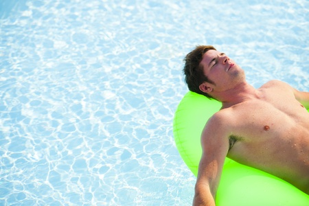 Young man relaxing and floating on pool photo