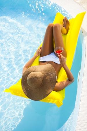 Junge Frau liegt entspannt auf Pool mit Getränken