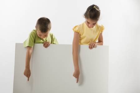 Two children holding a blank sign and looking at it; you can add your own text photo