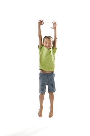 LIttle boy jumping on white photo