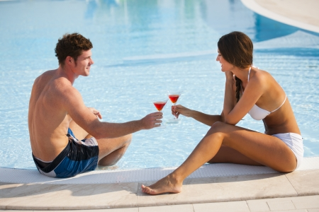 Happy couple enjoying thei drink by the pool photo