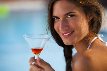 Smiling woman with drink by the pool photo