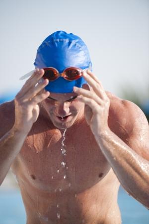 Male swimmer adjusting swimming goggles photo