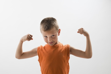 boy muscles: Little boy showing his muscles, white background