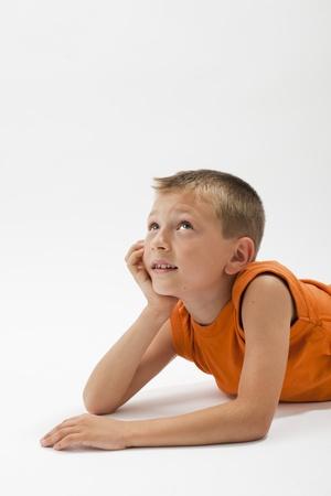 Pensive little boy lying on the floor