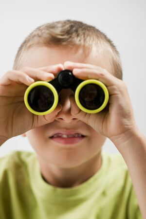 Little boy with binoculars, white background photo