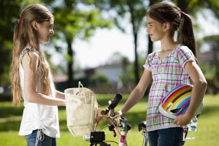 children only: Two little girls with bike outdoors Stock Photo