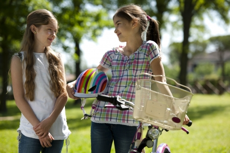 Two little girls with bike outdoors photo