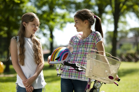two people only: Two little girls with bike outdoors Stock Photo
