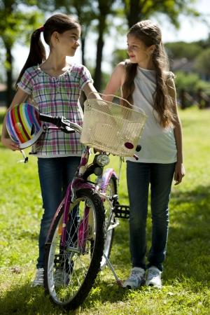 Two little girls with bike outdoors Foto de archivo
