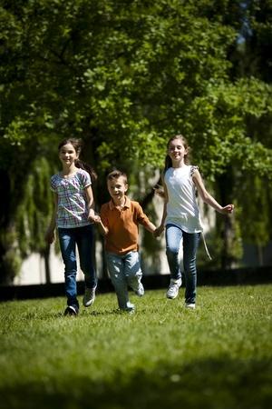 niños jugando en el parque: Niños corriendo en el parque Foto de archivo
