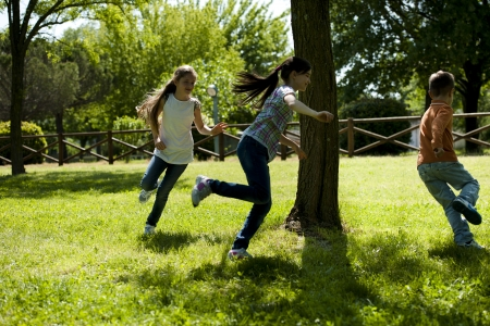 ni�os jugando en el parque: Peque�o grupo de ni�os que jugaban corriendo alrededor de un �rbol, jugar a la mancha Foto de archivo