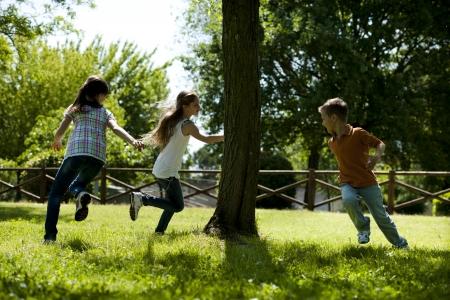 niños jugando en el parque: Pequeño grupo de niños que jugaban corriendo alrededor de un árbol, jugar a la mancha Foto de archivo