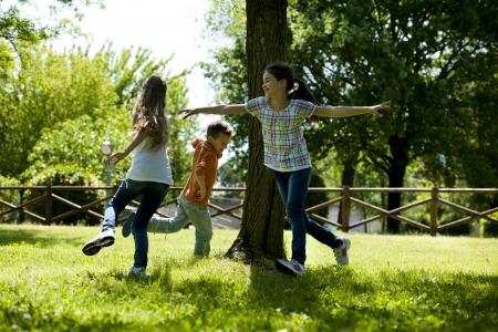 Kleine groep van spelende kinderen lopen rond een boom, het spelen tag