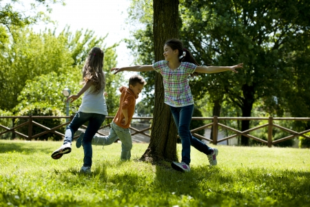 moving images: Small group of children playing running around a tree, playing tag