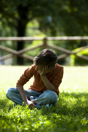 bulling: Triste  preocupada ni�o sentado al aire libre