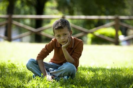 bulling: Triste  preocupada niño sentado al aire libre