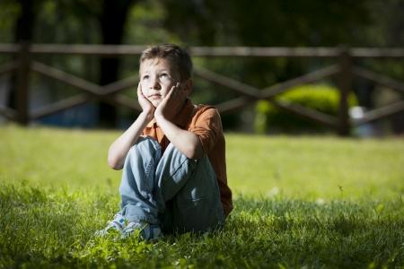 bulling: Little boy profundo en los pensamientos Foto de archivo