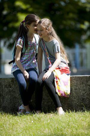 niÑos hablando: Dos niñas susurrando secretos mientras estaba sentado al aire libre