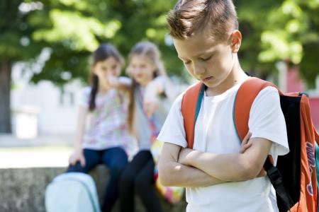 Zwei kleine Mädchen Pöting an dem kleinen traurigen Jungen, Fokus auf den Vordergrund Standard-Bild