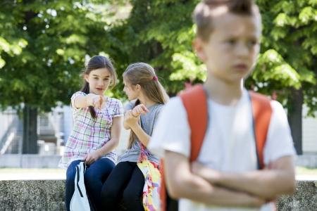Two little girls poting at the little sad boy, focus on background Standard-Bild