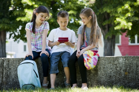 Children playing video games outdoors photo