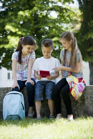 niños jugando videojuegos: Los niños que juegan juegos de video al aire libre Foto de archivo