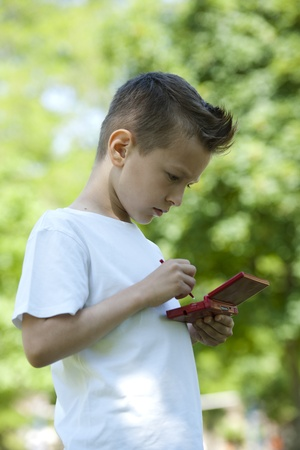 Little boy with handheld videogame outdoors photo