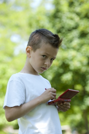 Little boy playing with is videogame outdoors Imagens - 15455324