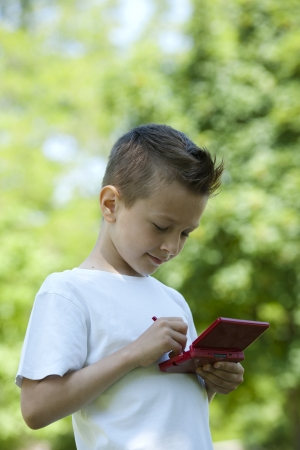 videogame: Little boy playing with is videogame outdoors Stock Photo