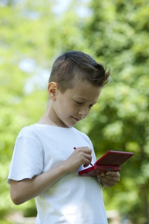 Little boy playing with is videogame outdoors photo