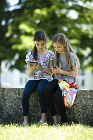 only girls: Little friends with PC tablet and mobile phone Stock Photo