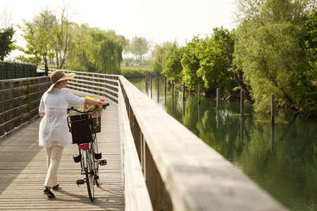 walling: Woman with bike by river Stock Photo