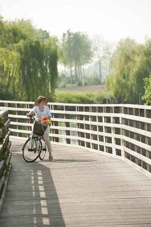 walling: Woman ciclying on a wooden bridge Stock Photo