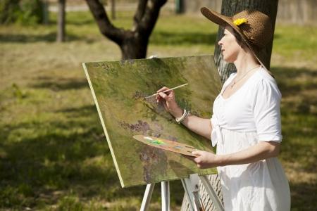 Vrouw genieten van het schilderen buiten Stockfoto