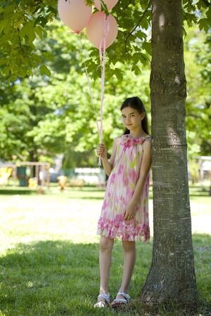 helium balloon: Cute little girl with pink balllons, standing outdoors