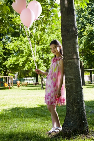 Cute little girl with pink balllons, standing outdoors photo