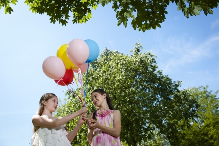 Two girlfriends with balloons having fun outdoors photo