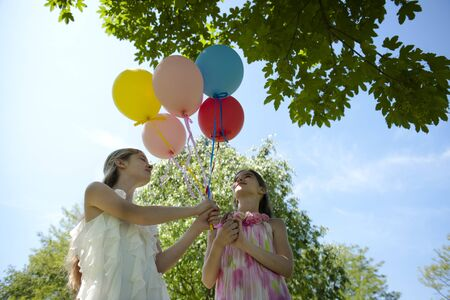 ballons: Two girlfriends with balloons having fun outdoors