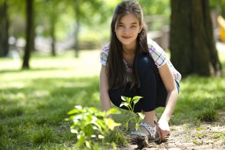 plantando un arbol: Ni�a plantar un �rbol, mirando a la c�mara