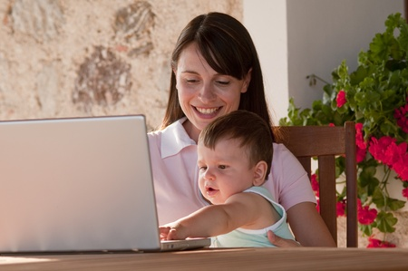 madre trabajando: Madre que trabaja en el país que sostiene a su bebé